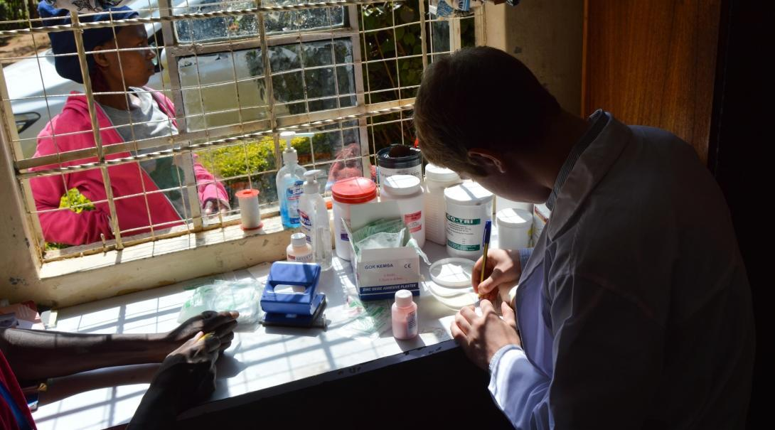 A local doctor is pictured organising medical prescriptions whilst a placement student with projects abroad whilst on her pharmacy internship in Ghana watches over.